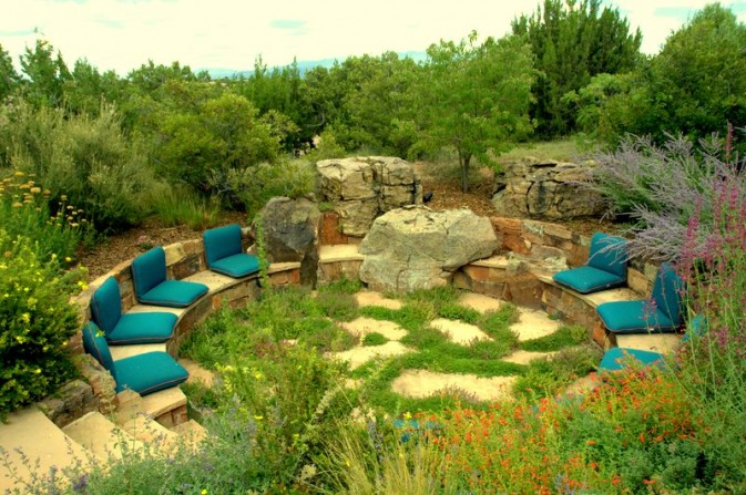 blue cushions, santa fe gardens, flagstone, fire pit, stone work, thyme joints, character boulders, red flowers