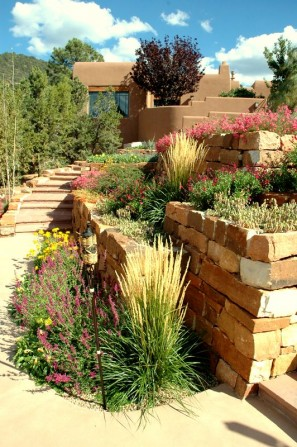 stone steps,tiki torch, terrace, terraced walls, poolside garden, pool, tumbling flowers, southwestern style garden, stone work, natural stone, rock work, stone walls, masonry walls